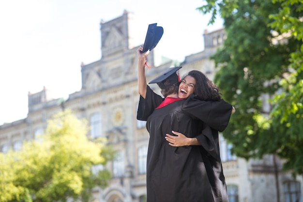 Happy graduates. friends hugging each other after graduation and feeling happy