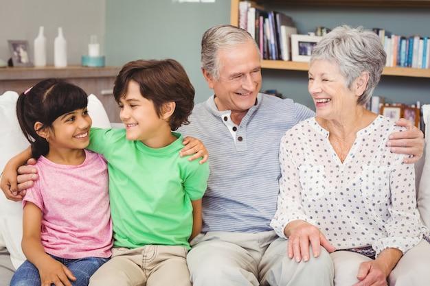 Happy grandchildren with grandparents on sofa at home