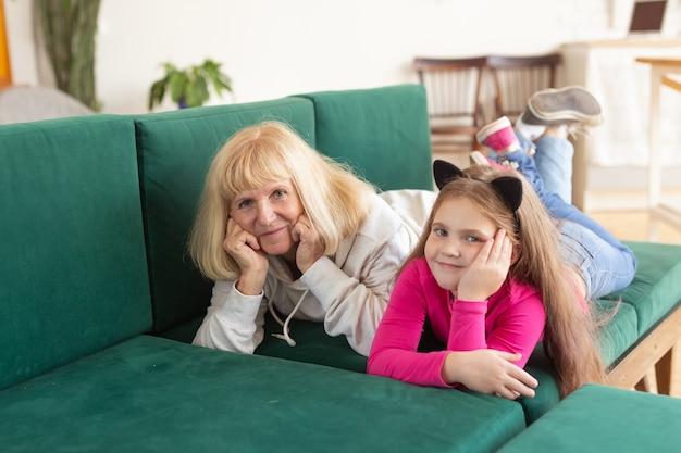 幸せな孫娘とおばあちゃんが面白いポーズでソファに横たわっています。家で孫と楽しんでいるおばあちゃん。高齢者、家族、世代の概念。