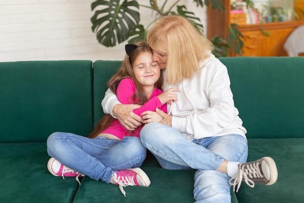 面白いポーズでソファに座っている幸せな孫娘と祖母おばあちゃんは家で孫を抱きしめます