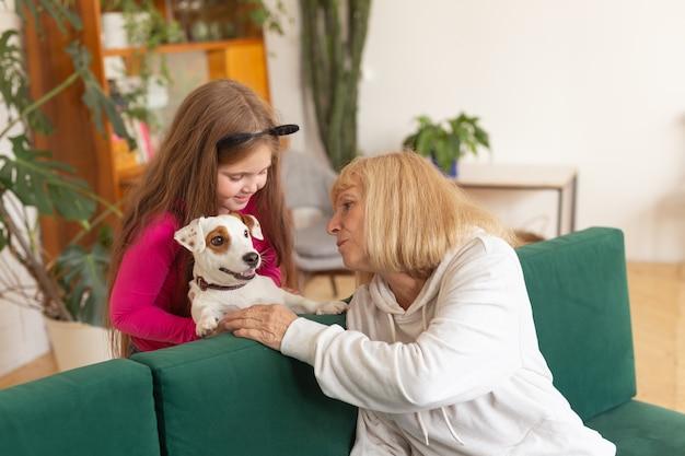 ジャックラッセルテリア犬と一緒にソファに座っている幸せな孫娘と祖母。おばあちゃんは家で孫を抱きしめます。高齢者、家族、世代の概念。