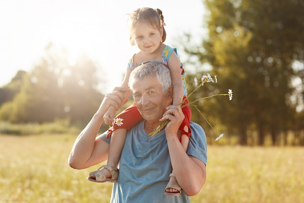 幸せな祖父と孫娘は屋外で一緒に楽しんでいます。灰色の髪の男性が小さな子供にピギーバックの乗車を与える