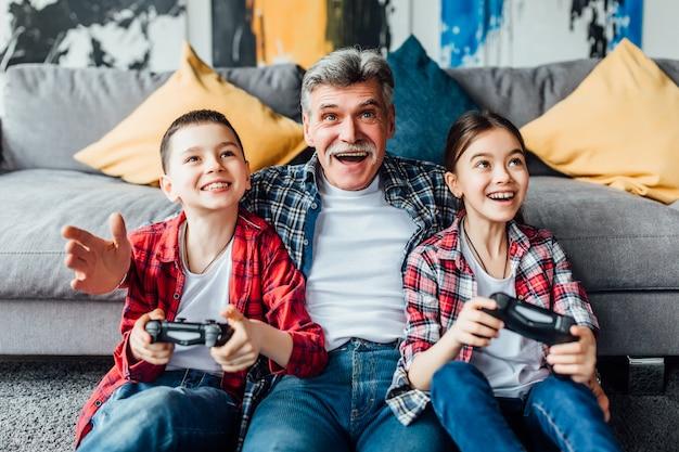 Счастливый дедушка и дети играют в видеоигры, лежа на полу у себя дома.
