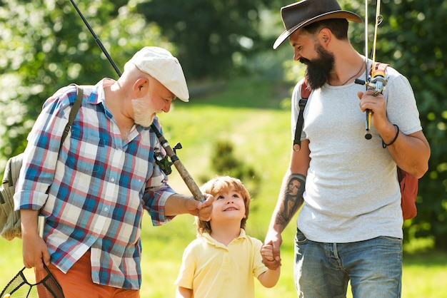Happy grandfather, father and grandson with fishing rods