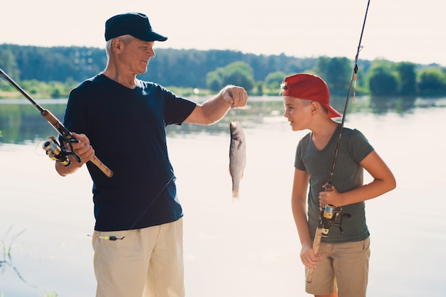 Happy grandfather and grandson fishing on river.