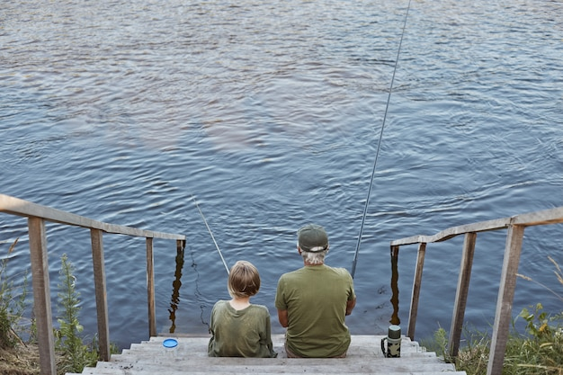Happy grandfather and grandson fishing together, sitting on wooden placing near river, holding fishing rod in hands