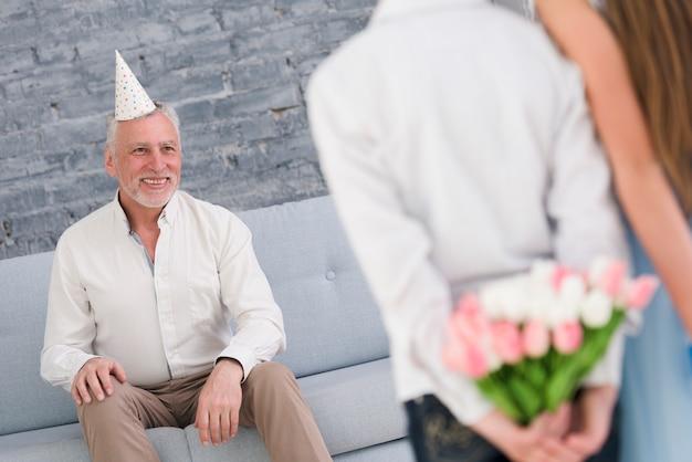 Счастливый дедушка смотрит на своих внуков, прячущих подарки за спиной
