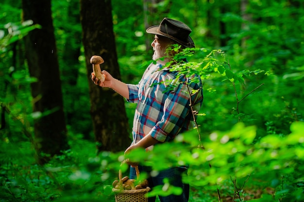 Happy grandfather picking mushrooms