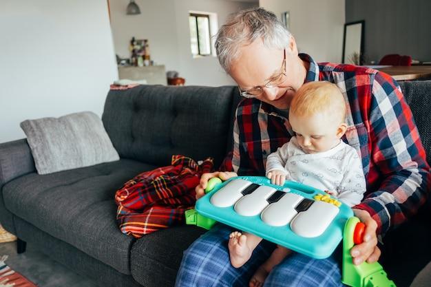 リビングルームで女の赤ちゃんと遊んで幸せな祖父