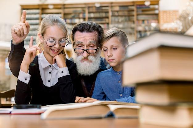 오래 된 빈티지 라이브러리에서 테이블에 앉아 손자와 손녀와 함께 행복 한 할아버지 읽기 책. 노인과 소녀는 손가락을 가리키고 웃고있다.