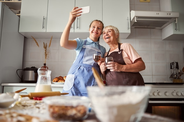 부엌에서 셀카를 찍는 행복한 할머니와 귀여운 소녀