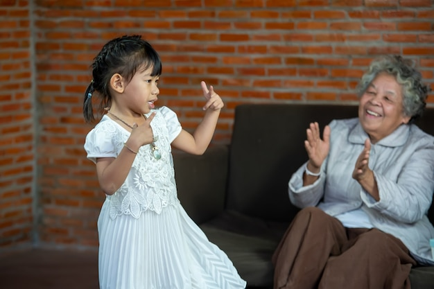 Happy grandma with granddaughter,little granddaughter dancing in living room enjoy priceless time together at funny weekend activities concept.