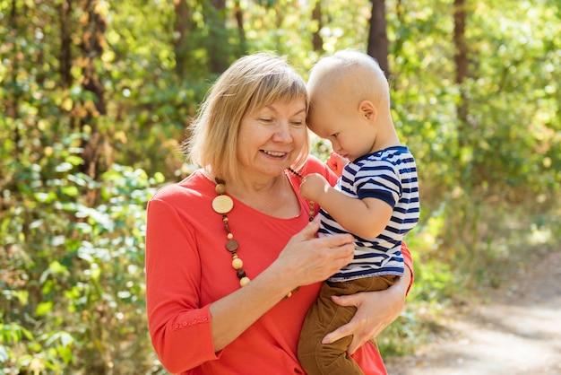 Счастливая бабушка с внуком, обнимая открытый