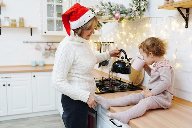 クリスマスのキッチンでお茶を飲む幸せな祖母と孫娘