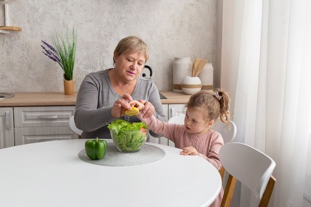 Счастливые бабушка и внучка вместе готовят салат на светлой кухне. семья готовит здоровую пищу.