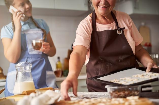 그녀의 손녀와 부엌에서 쿠키를 굽고 행복 할머니
