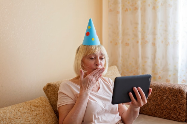 Happy grandmother celebrating birthday together with her family via internet in quarantine time