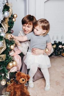 彼女の孫娘とクリスマスを祝う幸せな祖母