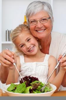 孫娘とサラダを食べるおばあちゃん