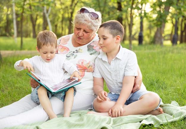 Счастливая бабушка обнимает внуков. бабушка с внуками