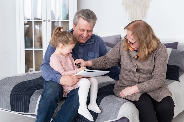 Счастливая бабушка, дедушка и внучка рисуют карандашом, сидя на кровати. маленькая милая девушка с альбомом, сидя на коленях у дедушки