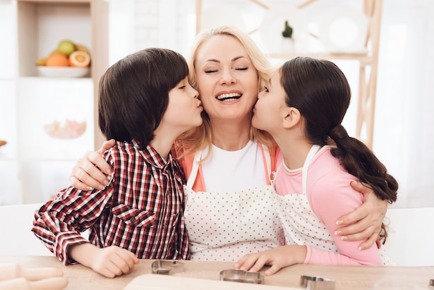 Счастливая бабушка обнимает внуков на кухне