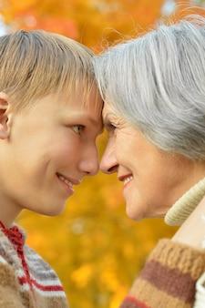 秋の公園で休んでいる男の子と幸せな祖母