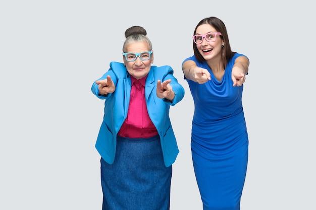 Счастливая бабушка с внуком, указывая пальцами на камеру и улыбается. отношения в семье. внучка или дочь с бабушкой отношения. закрытый студийный снимок, изолированные на сером фоне