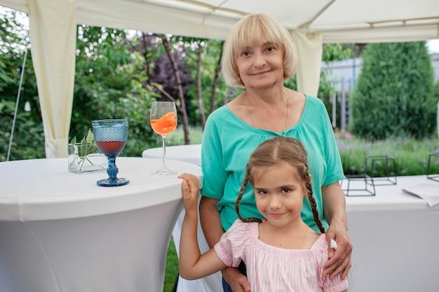 夏の幸せな先輩の裏庭の退職パーティーの間に彼女の孫と幸せな祖母