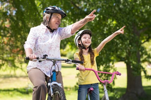 彼女の孫娘が自転車に乗っているおばあちゃん