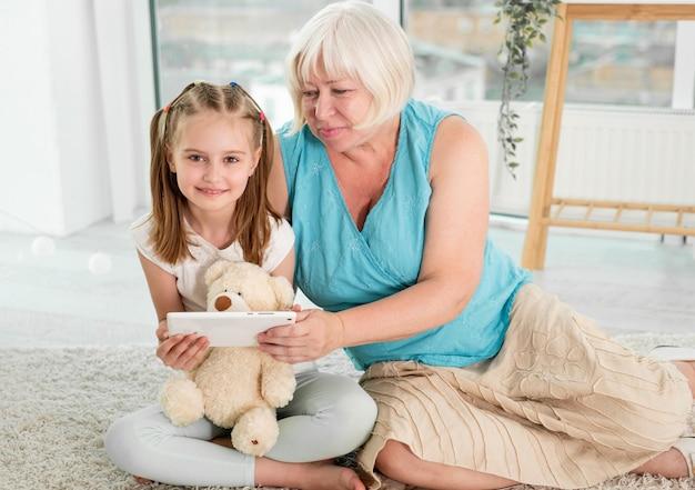 子供部屋の床にタブレットの立地を使用して小さな孫娘と幸せな祖母