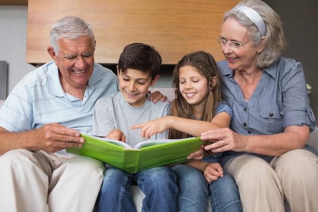 Счастливые дедушки и бабушки и внуки, смотрящие на альбомную фотографию
