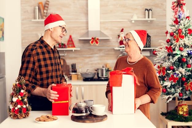 プレゼントを交換するクリスマスを祝う幸せな祖父母