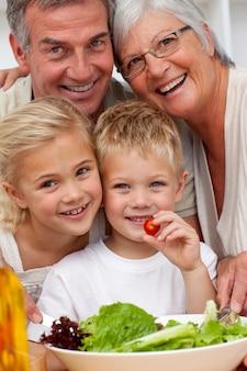 孫とサラダを食べる幸せな祖父母