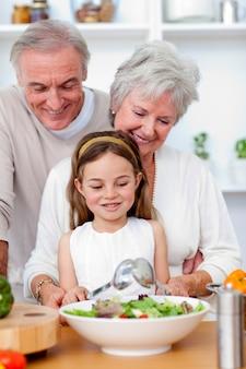 孫娘とサラダを食べる幸せな祖父母