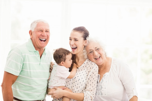 Happy grandparents playing with their grandson at home