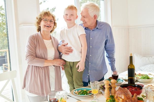 Счастливые бабушка и дедушка позирует с маленьким мальчиком