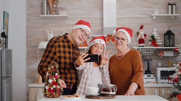 Smartpgoneを使用して自分撮りをしているクリスマスの装飾が施されたキッチンのテーブルに立っている幸せな祖父母