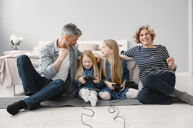 2 人の孫娘を持つ幸せな祖父母。ビデオゲームで遊ぶ家族。床に座っています。