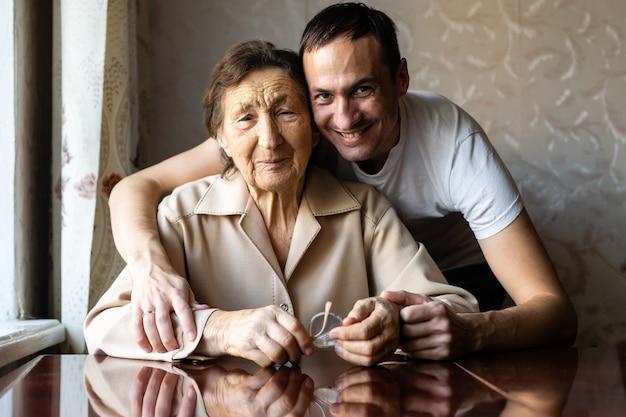 Happy grandson hugging her grandma at home