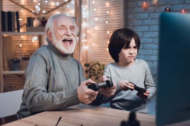 Happy grandson playing video game with grandfather