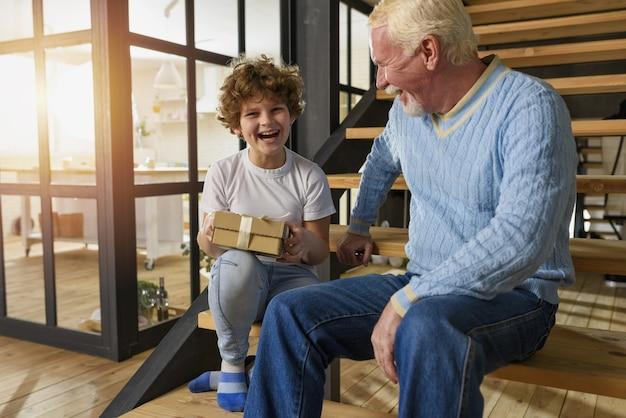 행복한 손자는 할아버지로부터 선물을받습니다. 즐거운 표현
