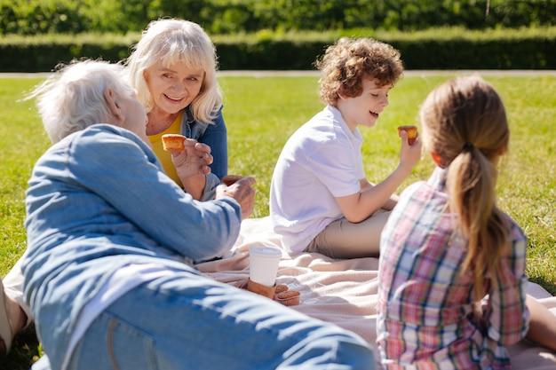 Счастливая бабушка держит сладости в левой руке во время кормления и смотрит на мужа