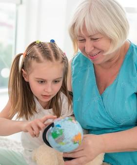 Счастливая бабушка показывает глобус внучке