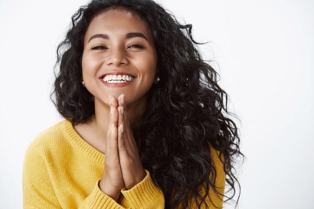 Счастливая благодарная молодая милая девушка благодарит за помощь, очень рада получить прекрасный подарок, радостно улыбается, сжимает ладони в молитве, стоит белая стена в желтом свитере