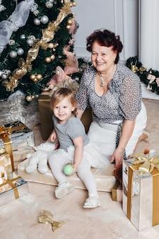 小さな女の子とクリスマスを祝う幸せな曽祖母