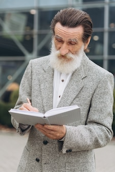 Happy grey-bearded man stand at the office buildings and writing notes in notebook.