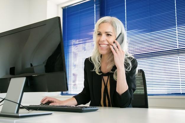 電話で同僚と話している幸せな白髪の実業家。チャット、笑顔、コンピューターでの作業に自信を持ってプロのマネージャー。ビジネス、職場、コミュニケーションの概念