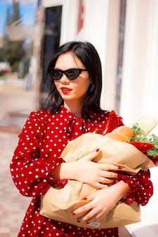 幸せな食料品の買い物客。食料品でいっぱいの紙の買い物袋を保持している赤いドレスの美しい伝統的な白人女性の肖像画。