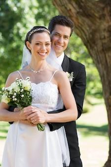 Happy groom embracing bride from behind in garden